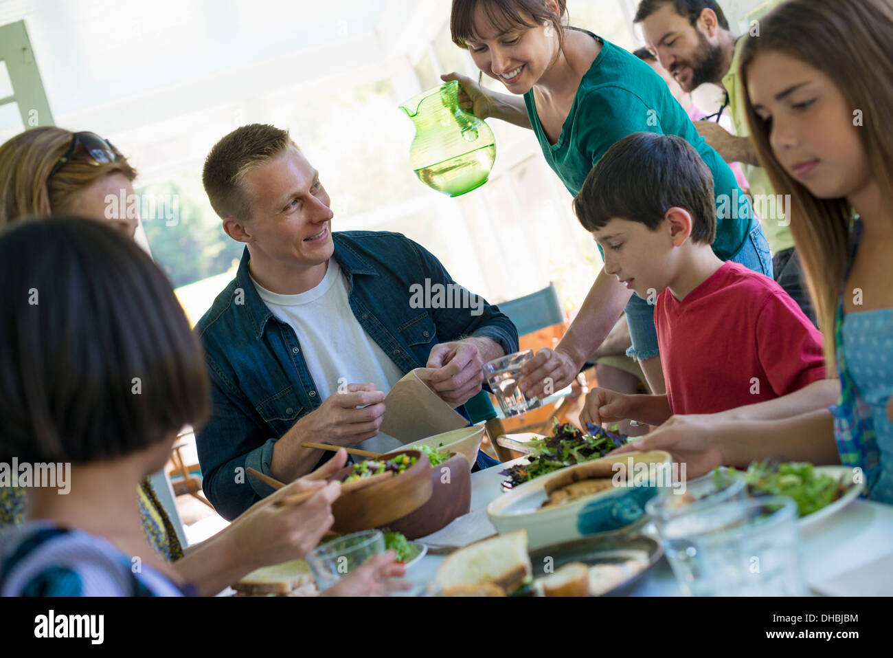A family party around a table in a cafe. Adults and children. - Stock Image