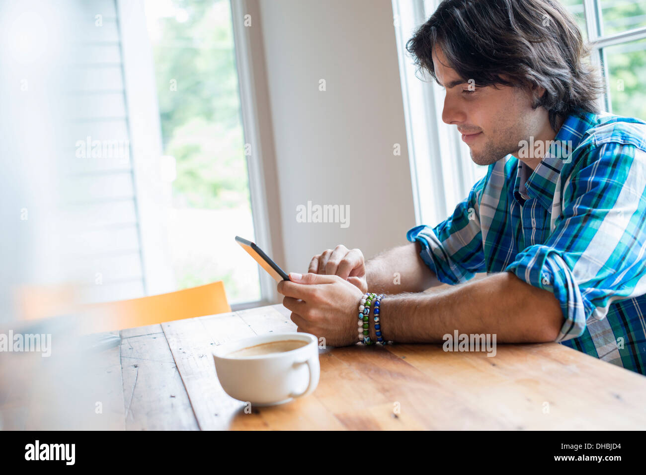 A man sitting in a cafe with a cup of coffee. Using a digital tablet. Stock Photo