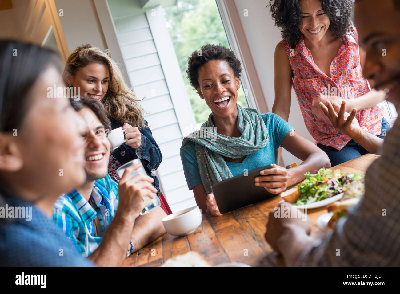 A group of people meeting in a cafe. Using digital tablets and smart phones. Having a meal together. - Stock Image