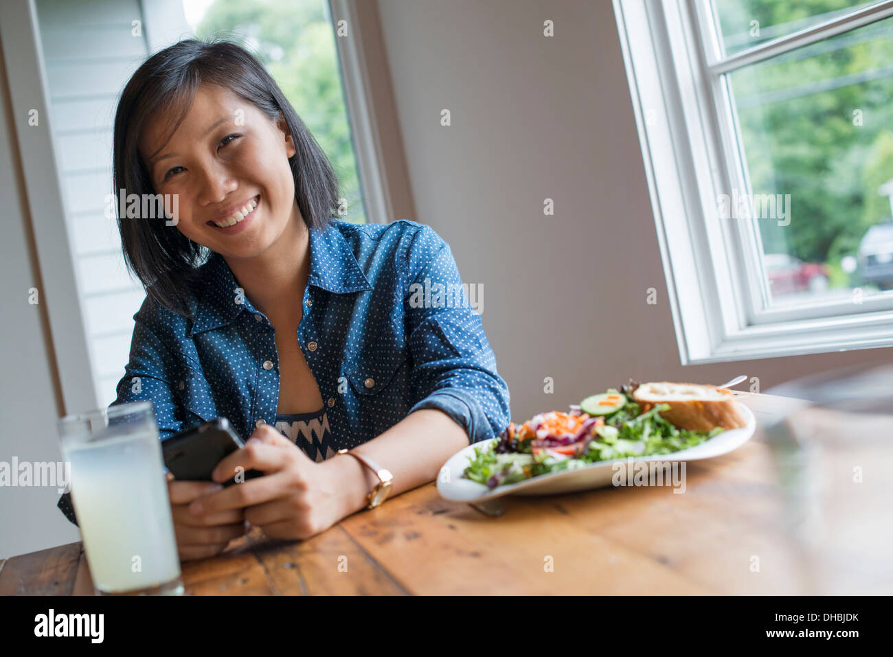 A young woman using a smart phone, seated at a table. Coffee and a sandwich. - Stock Image