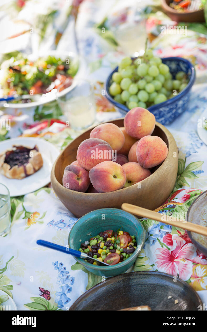 A garden table laid with a buffet of salad, fresh vegetables and fruit. - Stock Image