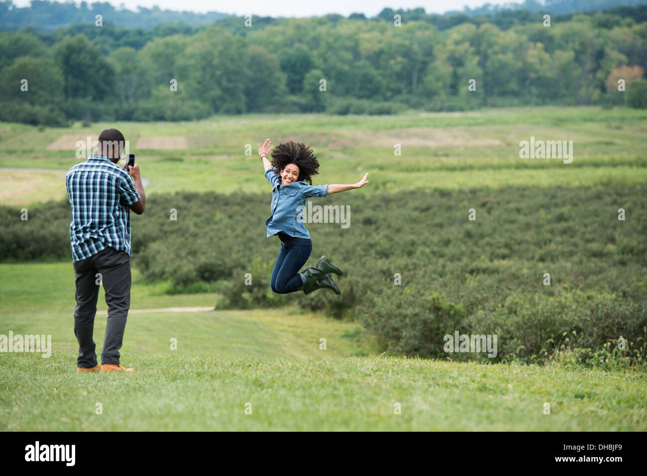 A man taking a photograph of a woman leaping in the air, jumping for joy with her arms outstretched. - Stock Image