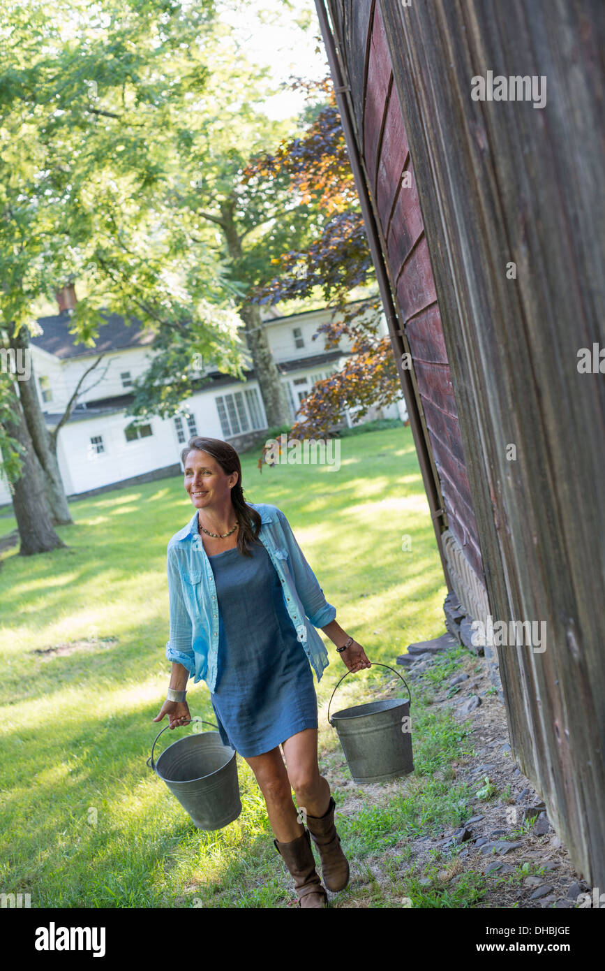 A woman carrying a bucket for animal feed in each hand, outside a barn. - Stock Image