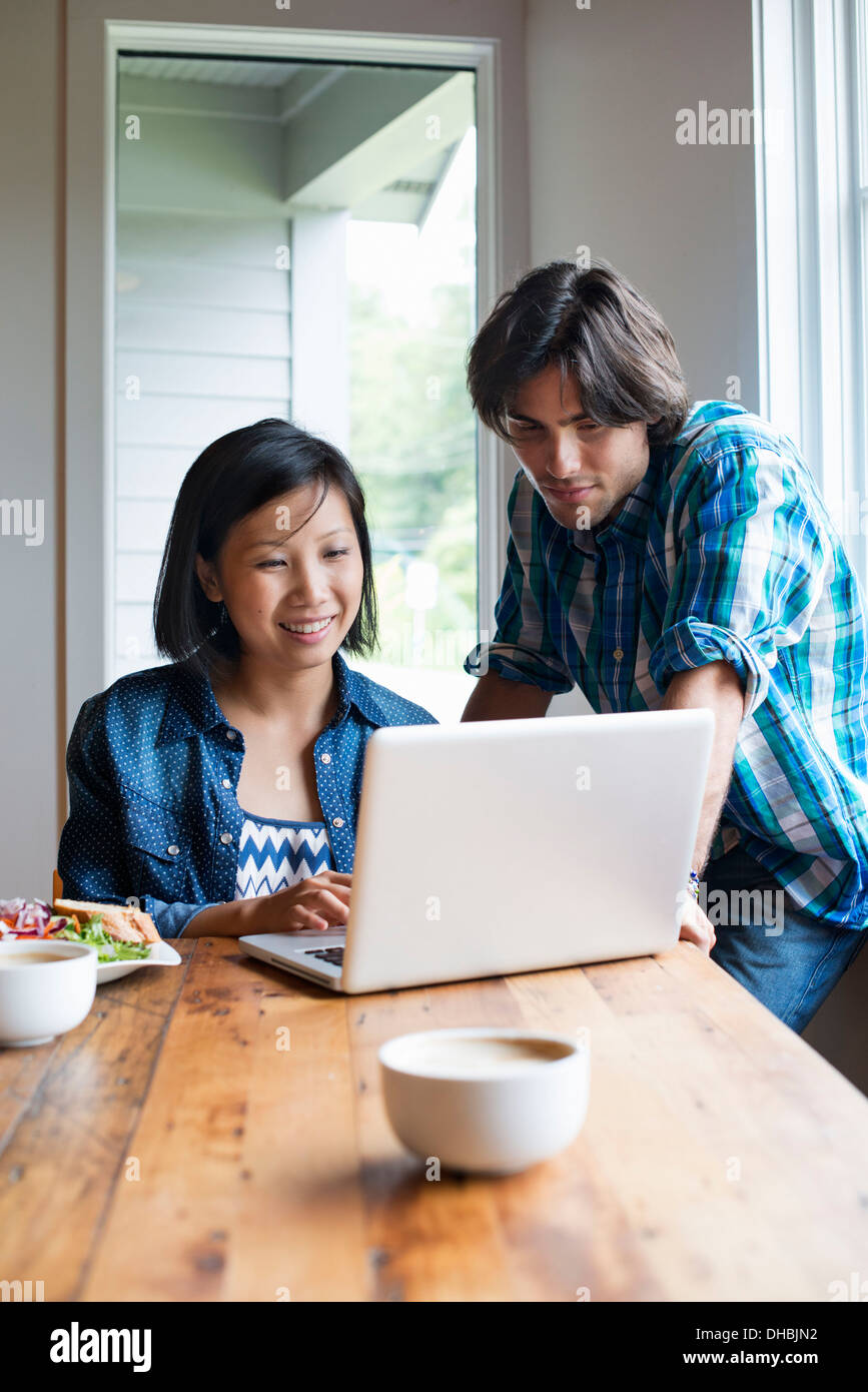 A man and woman using a laptop computer in a cafe. - Stock Image