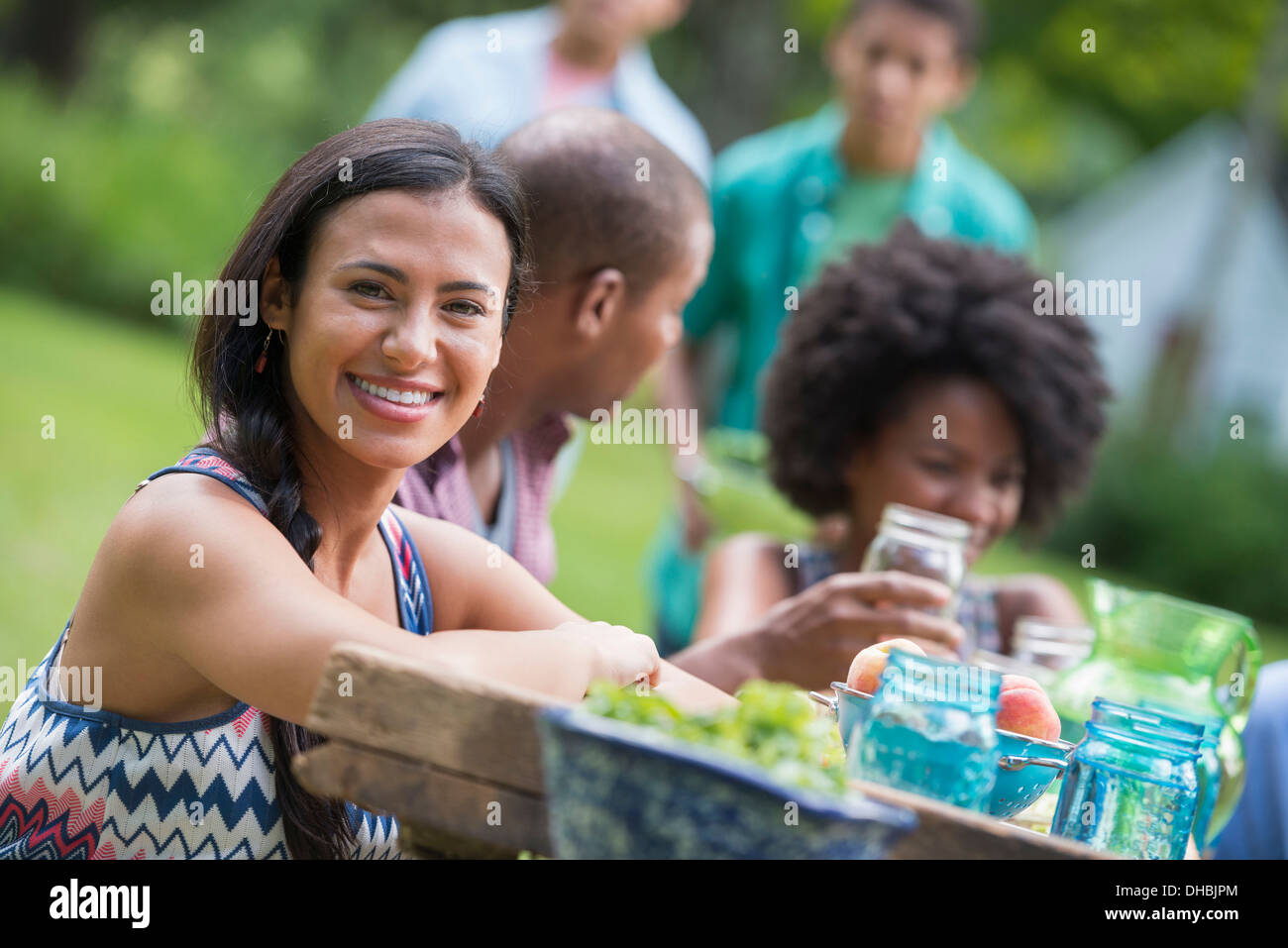 A group of adults and young people at a meal in the garden of a farmhouse. - Stock Image
