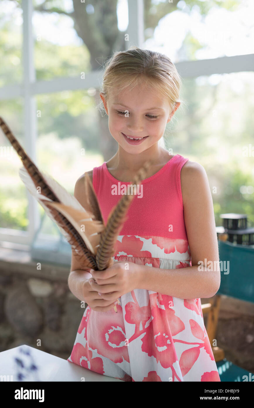 A young girl in a kitchen wearing a pink dress. Holding a bunch of bird feathers. Stock Photo