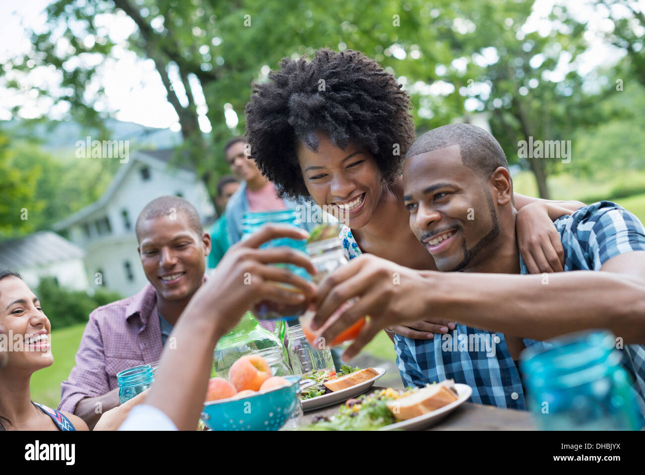 A group of adults and young people at a meal in the garden of a farmhouse. Passing plates and raising glasses. - Stock Image