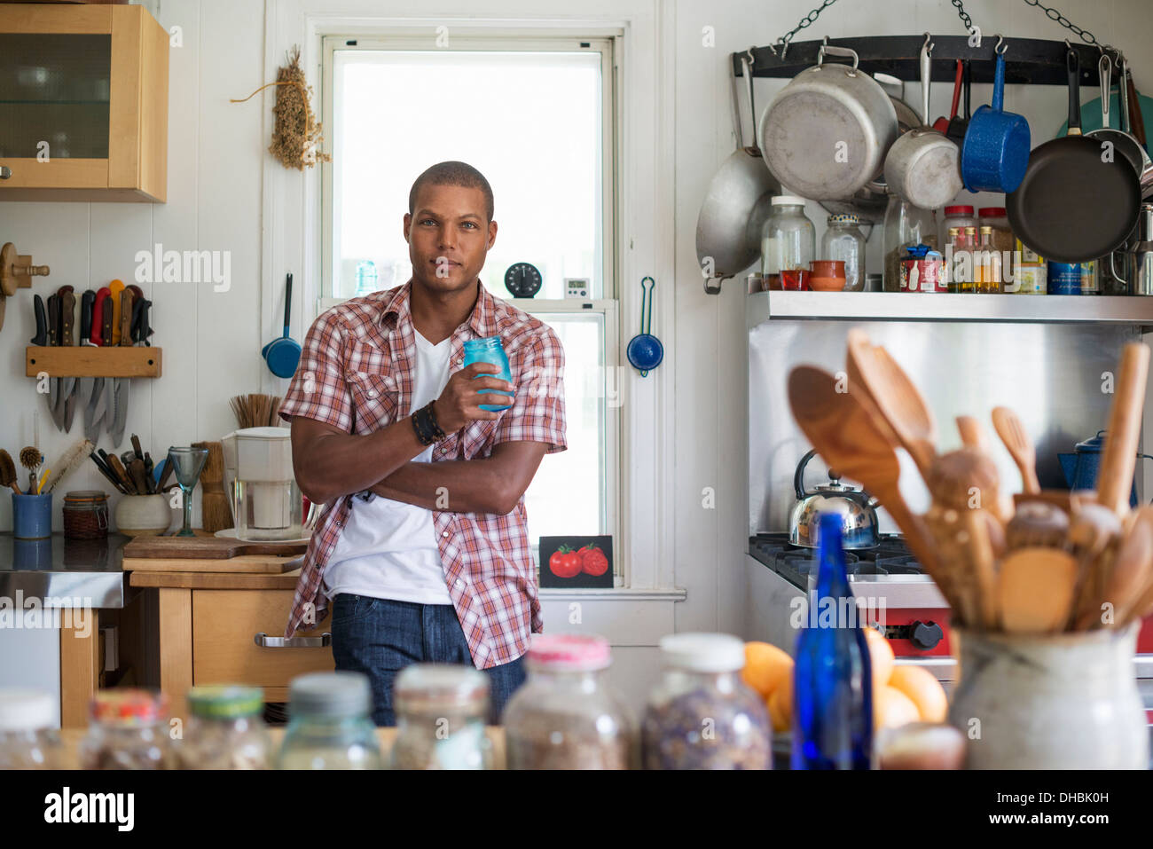 A man holding a drink standing in a farmhouse kitchen. - Stock Image