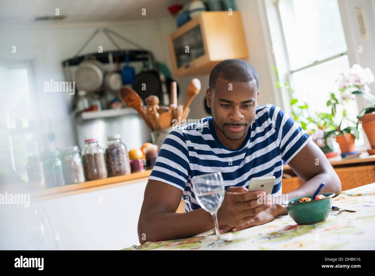 A man sitting at a table using a smart phone. Fruit dessert and a glass of wine at hand. - Stock Image
