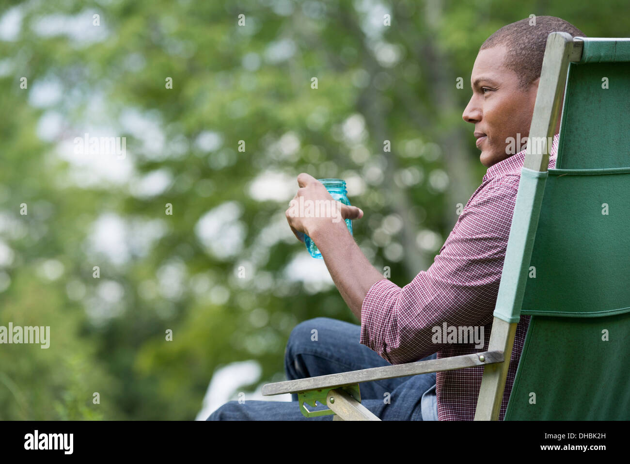 A man seated in a chair in a garden, relaxing. - Stock Image