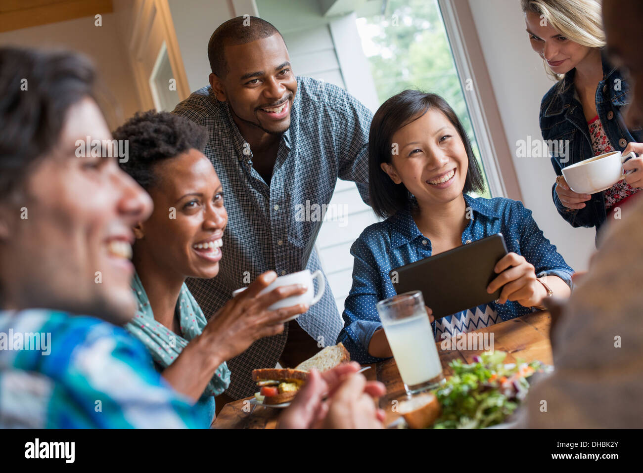 A group of people meeting in a cafe. Using digital tablets and smart phones. - Stock Image