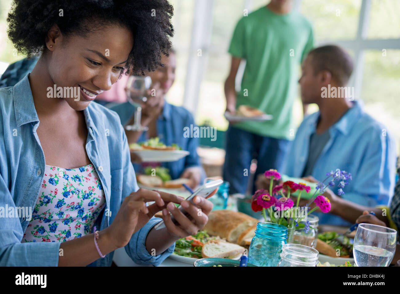 A group of women and men around a table sharing a meal in a farmhouse kitchen. - Stock Image