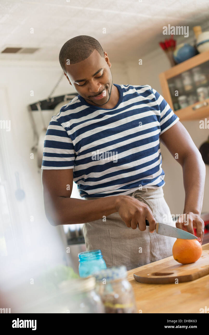 A man in a kitchen using a knife to slice an orange. - Stock Image