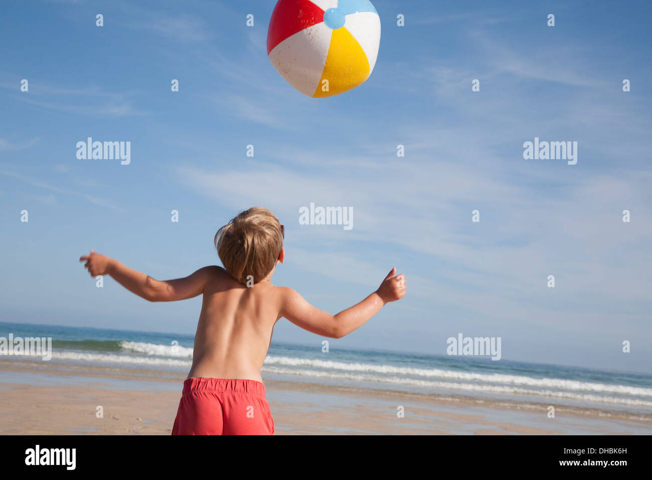 A boy in swimming trunks on the beach, with a large beach ball in the air above him. - Stock Image