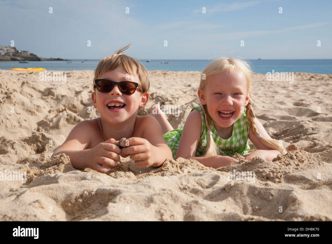 A boy and girl lying on their stomachs on the sand, laughing and looking at the camera. - Stock Image