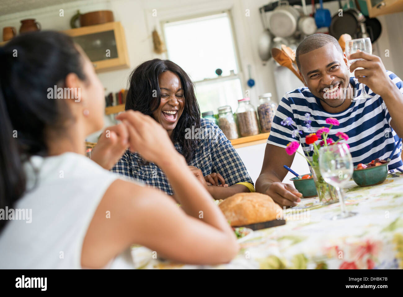 A group of women and men at a meal in a farmhouse kitchen. - Stock Image