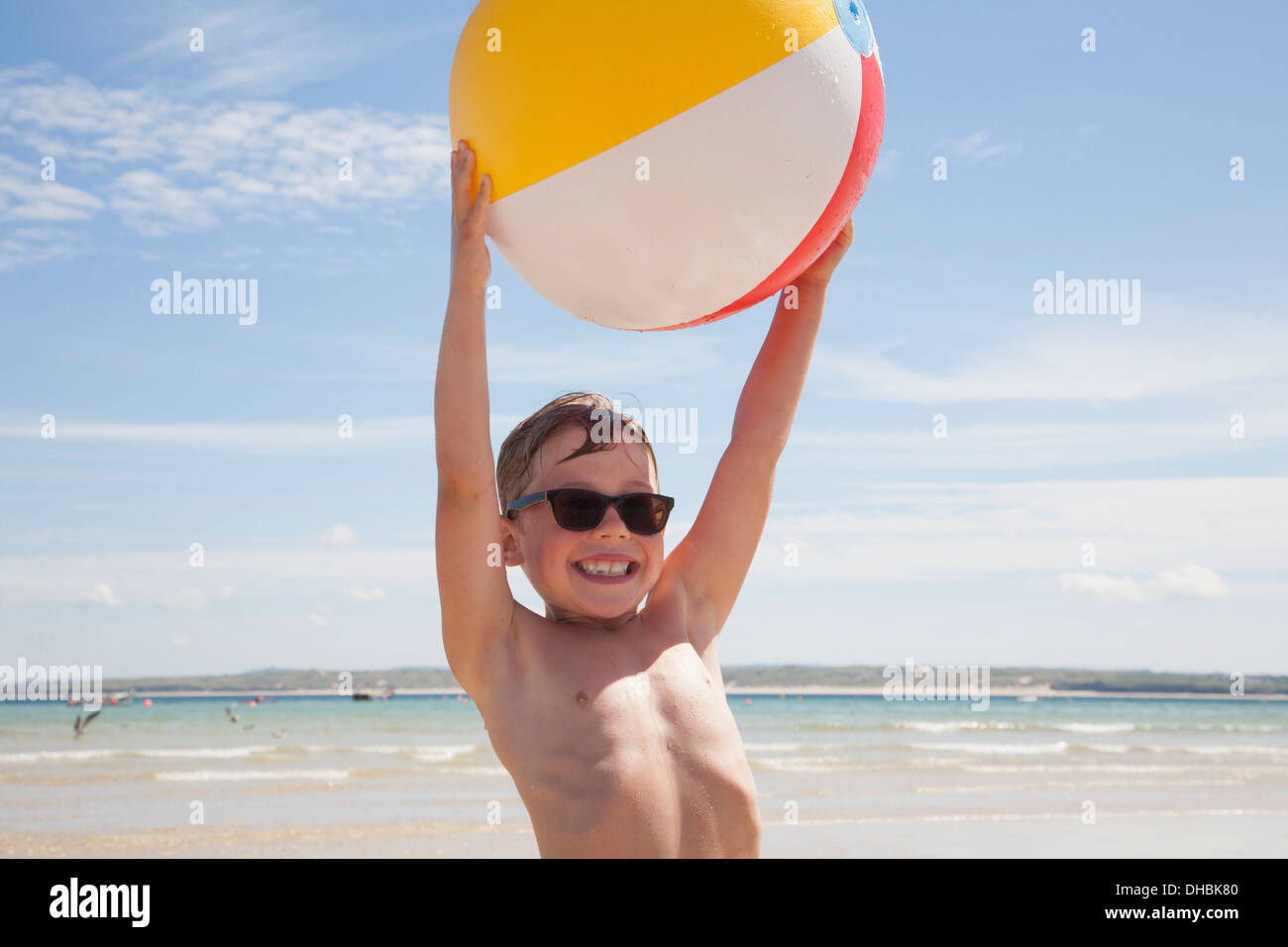 A boy wearing sunglasses on the beach. Holding an inflatable beach ball above his head. - Stock Image