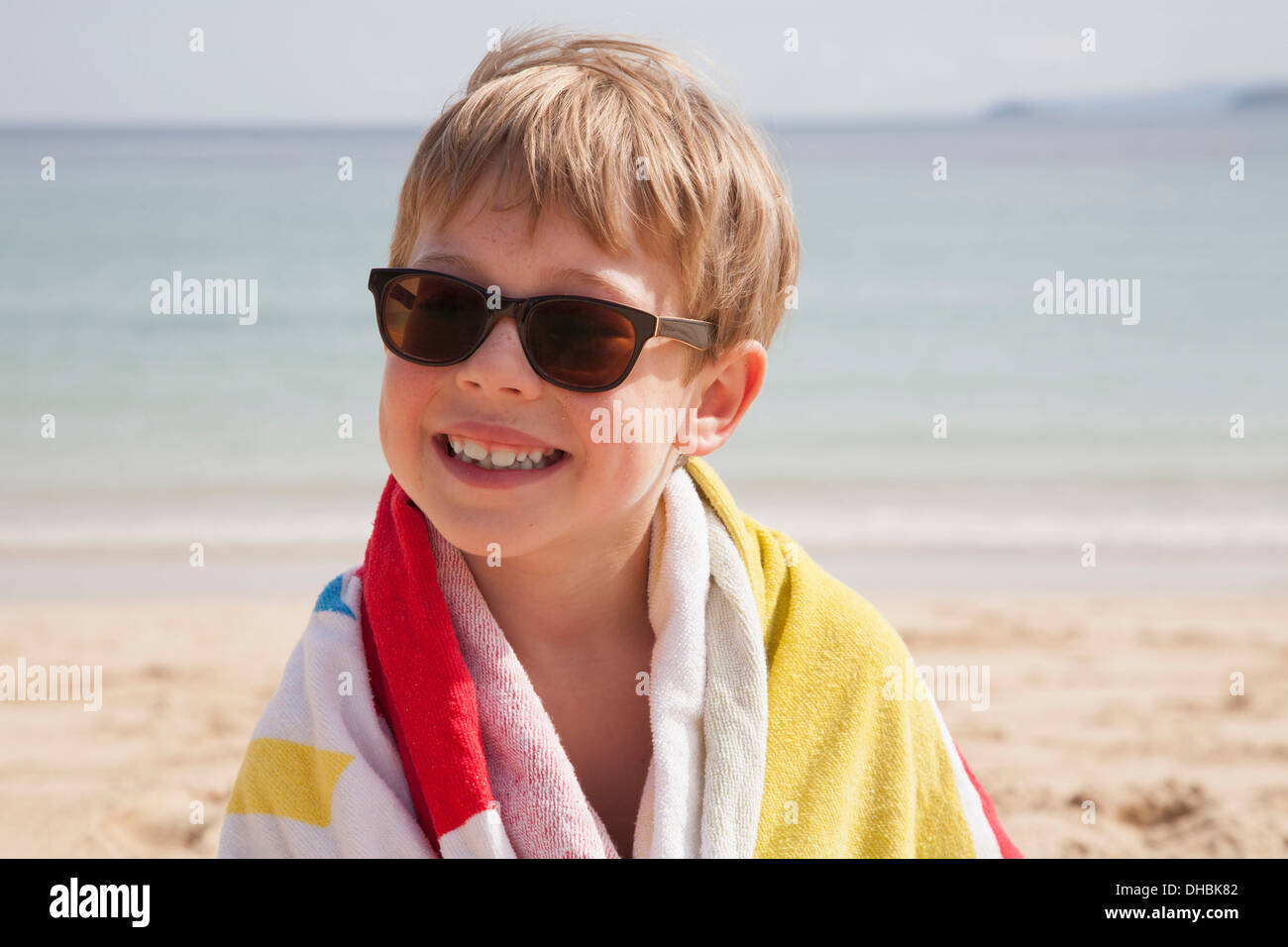 A boy in sunglasses on the beach, with a towel around his shoulders. - Stock Image