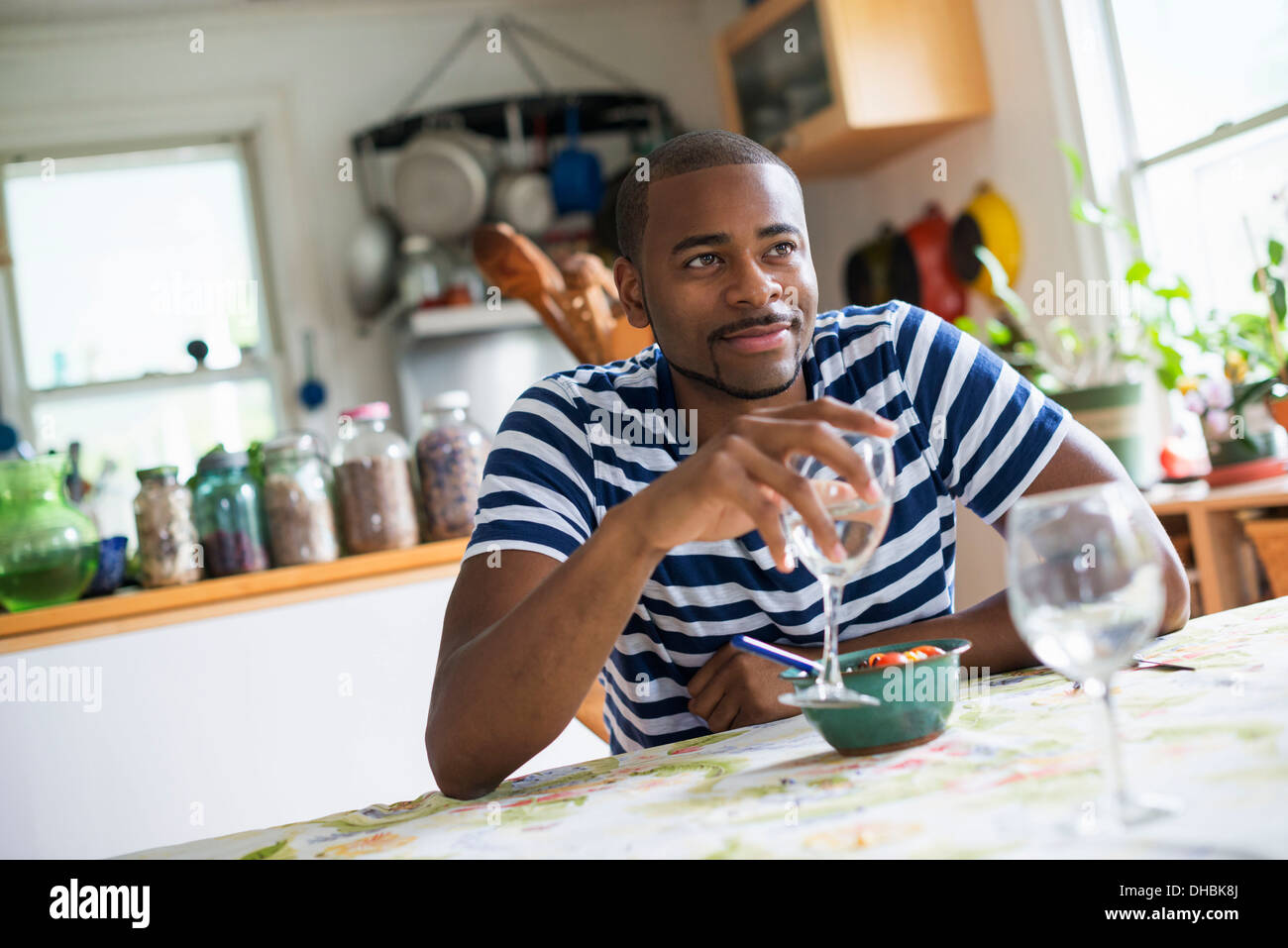 A man sitting at a table eating dessert, holding a glass of wine. - Stock Image