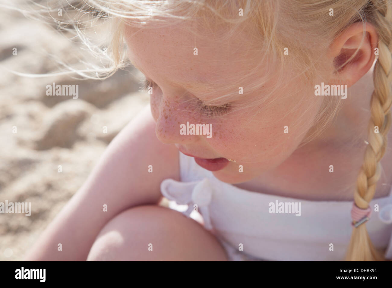A young girl with blonde hair in pigtails on the beach. - Stock Image