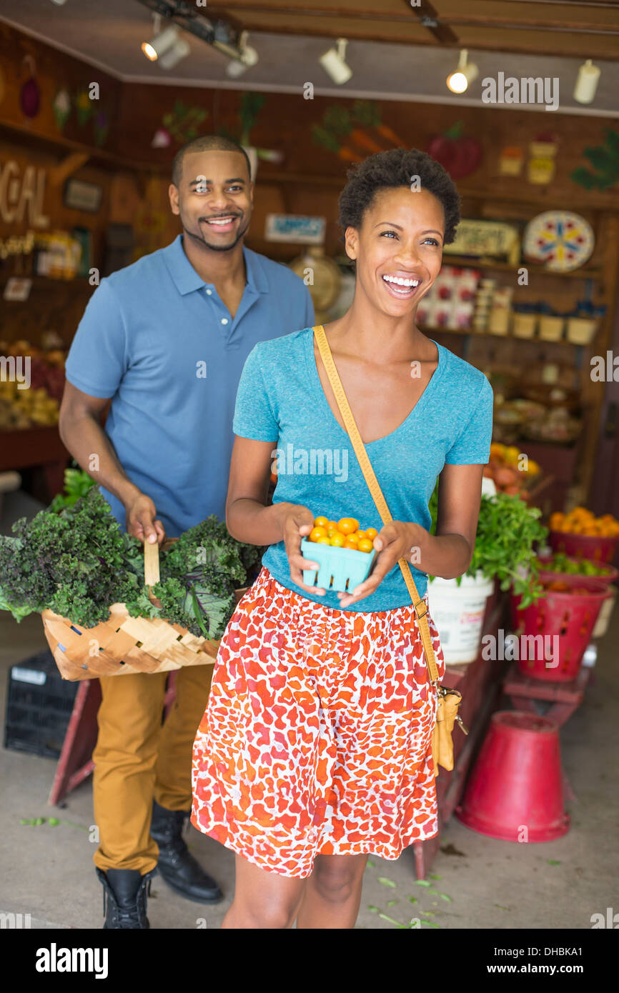 Two people in a farm shop, choosing organic vegetables. - Stock Image