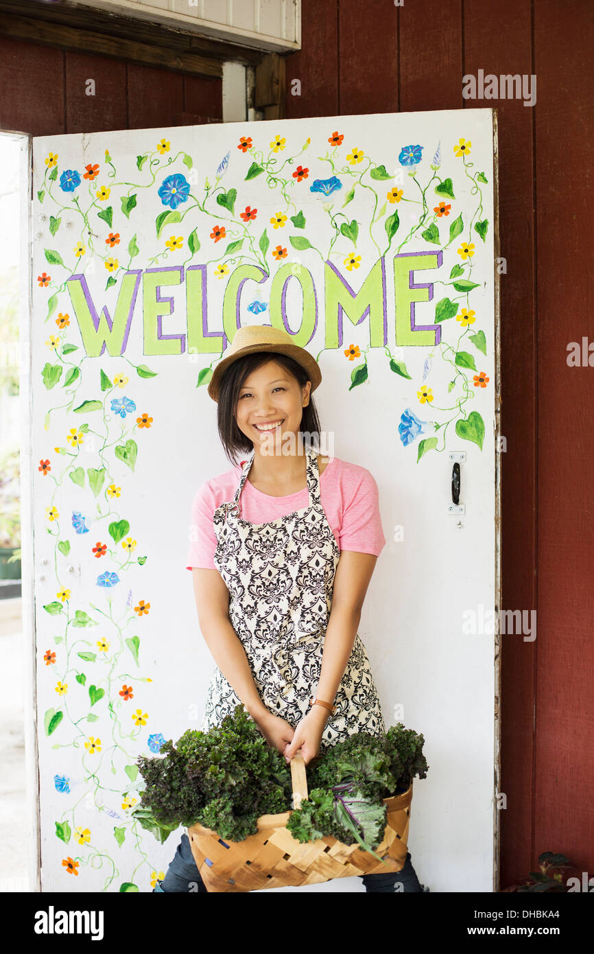 Working on an organic farm. A young Asian woman by the Welcome sign with a large basket of vegetables, freshly picked. - Stock Image