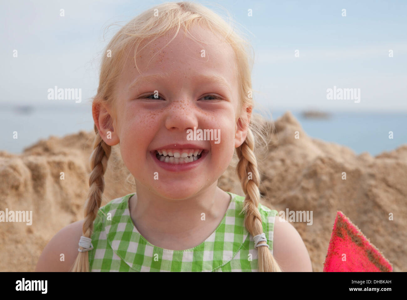 A girl beside a huge pile of sand on the beach, grinning at the camera. - Stock Image