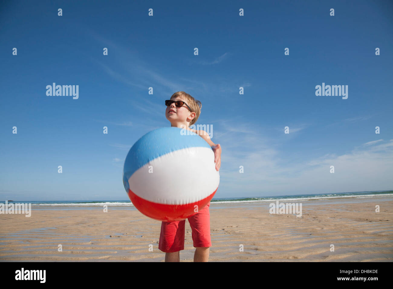 A boy on the beach holding a large inflatable beach ball. - Stock Image