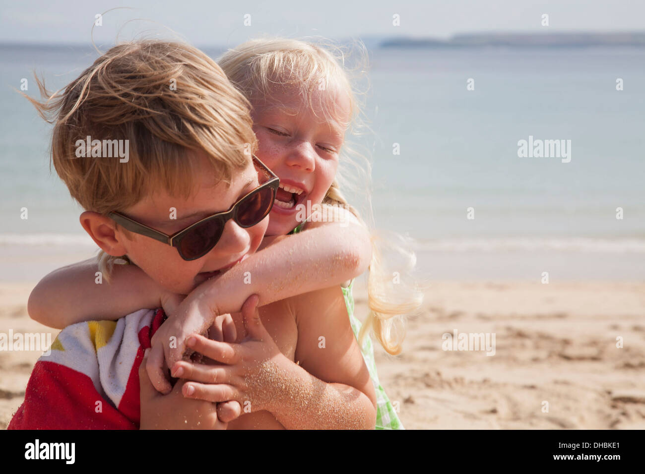 A brother and sister play fighting on the beach. A boy in sunglasses and a younger girl with her arms around his neck. - Stock Image