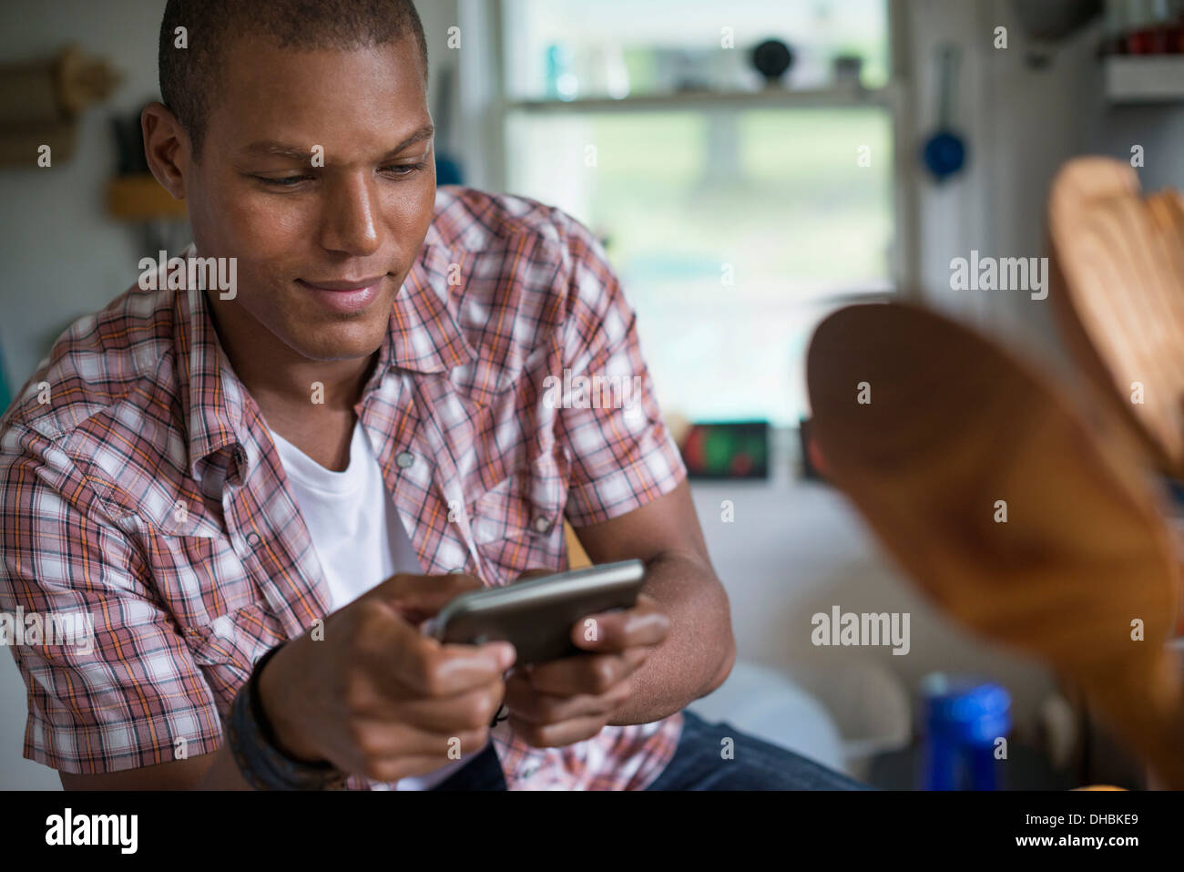 A man in a kitchen, using a digital tablet. - Stock Image