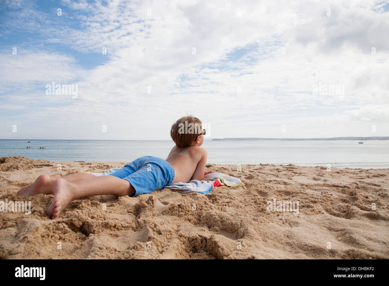 A boy lying on his front on the sand looking out to sea. - Stock Image