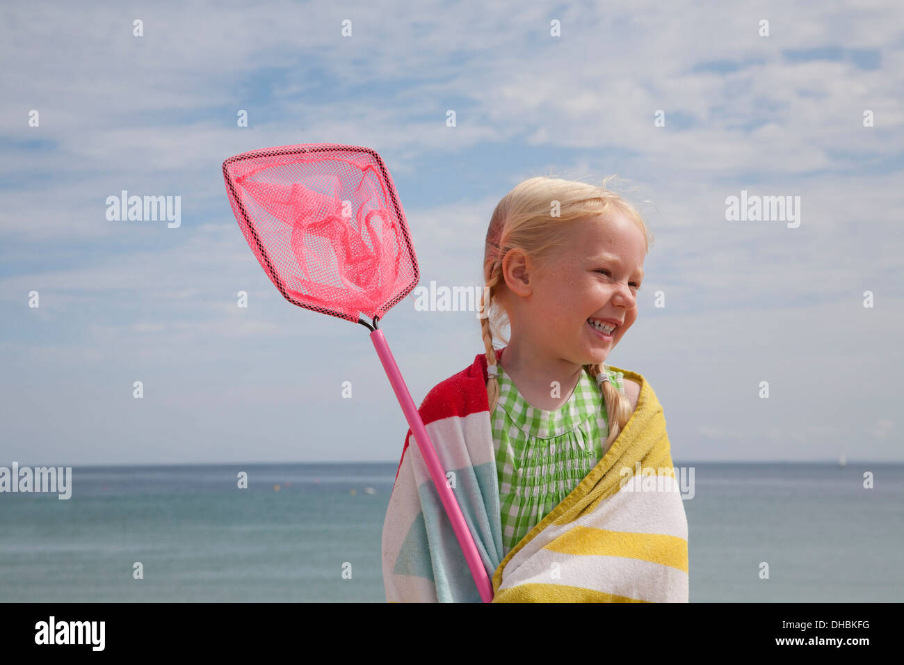 A young girl with a beach towel around her shoulders, carrying a small fishing net. - Stock Image