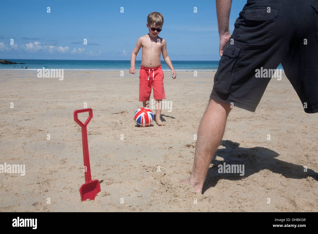 A boy playing football with a man on the sand. Father and son. A beach spade upright in the sand. - Stock Image