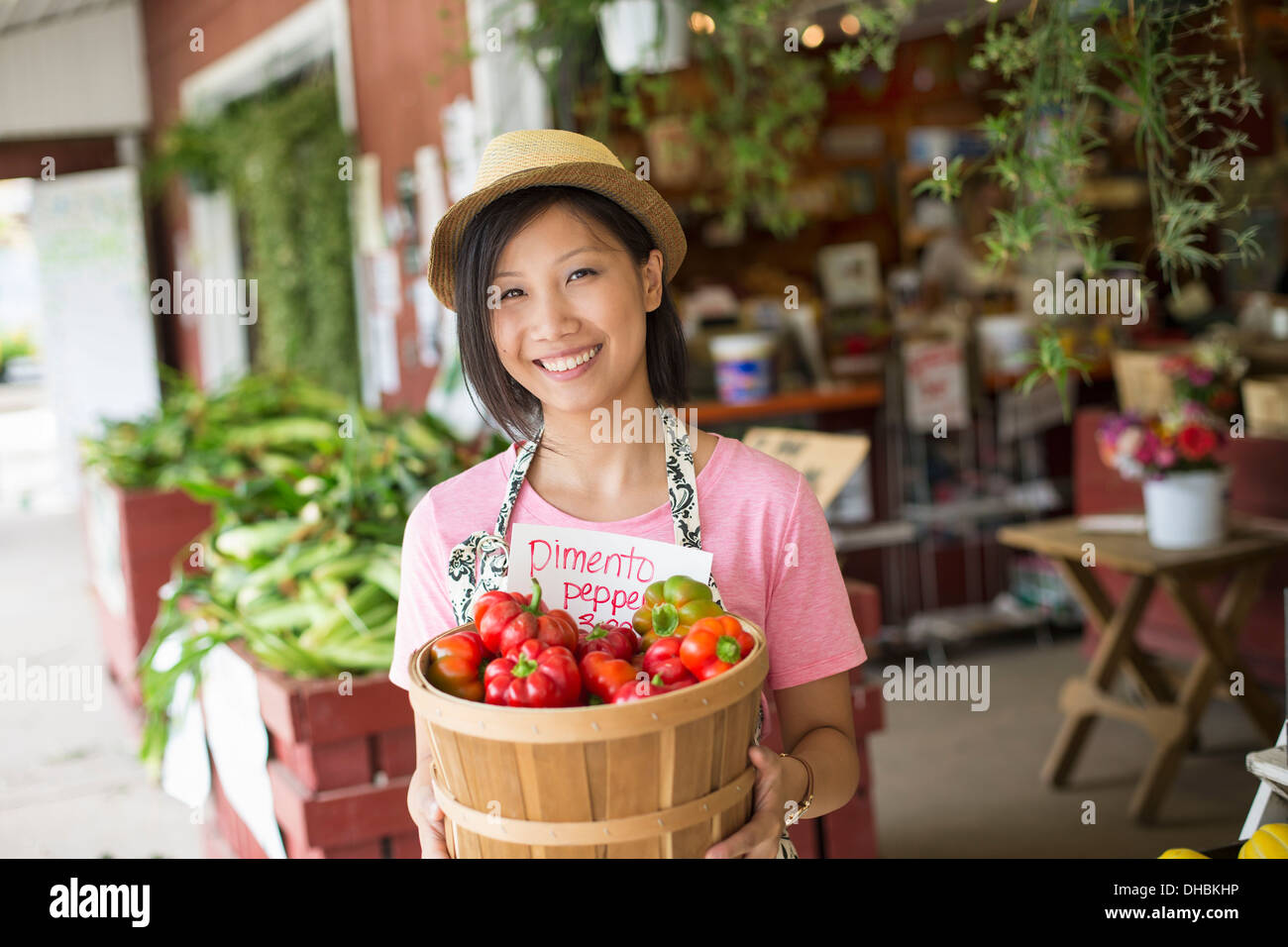 A woman working on an organic farm stand, displaying fresh vegetables for sale. - Stock Image