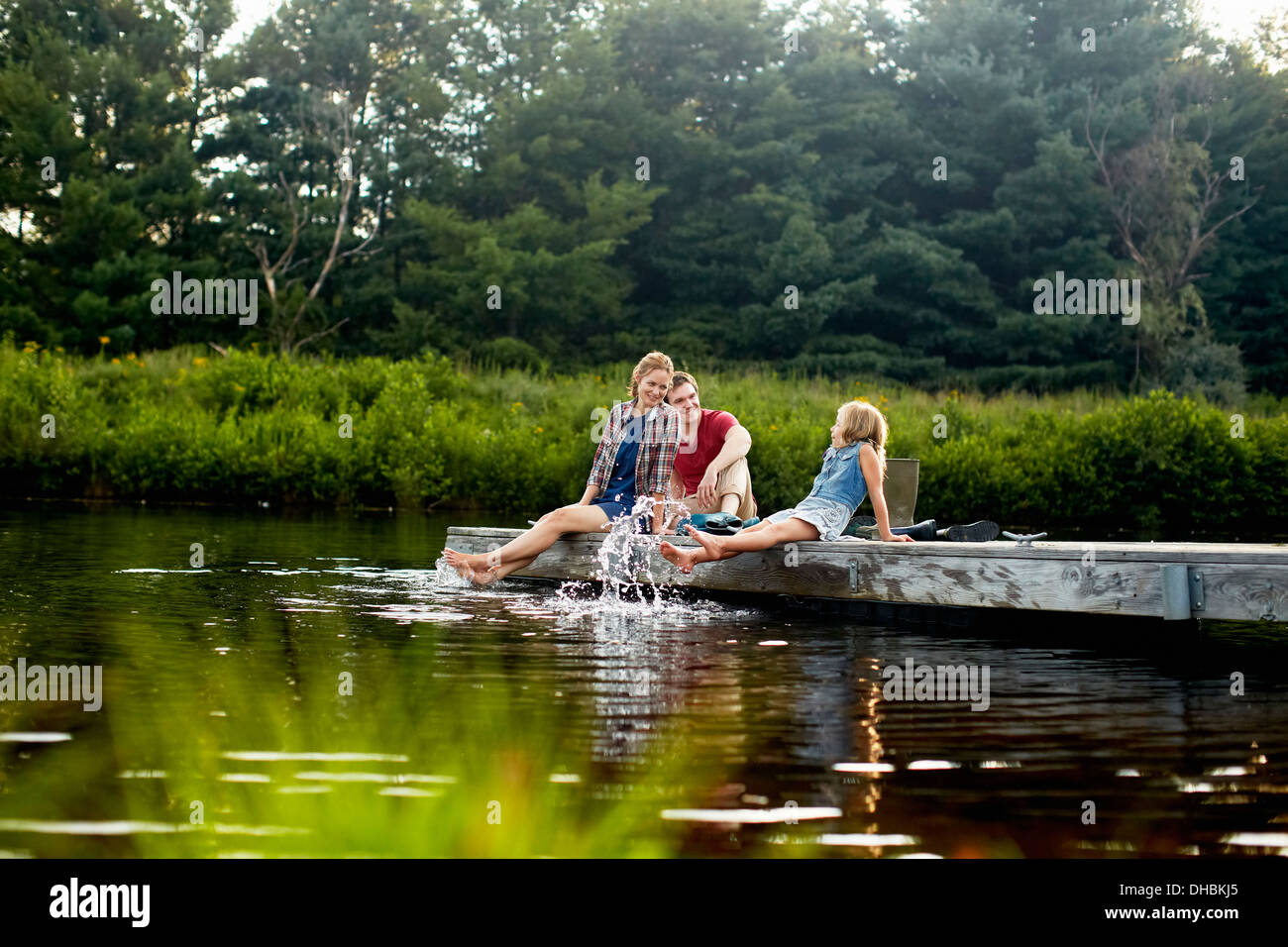 Three people, two adults and a child relaxing on a jetty, with their feet in the water at the end of a day. - Stock Image