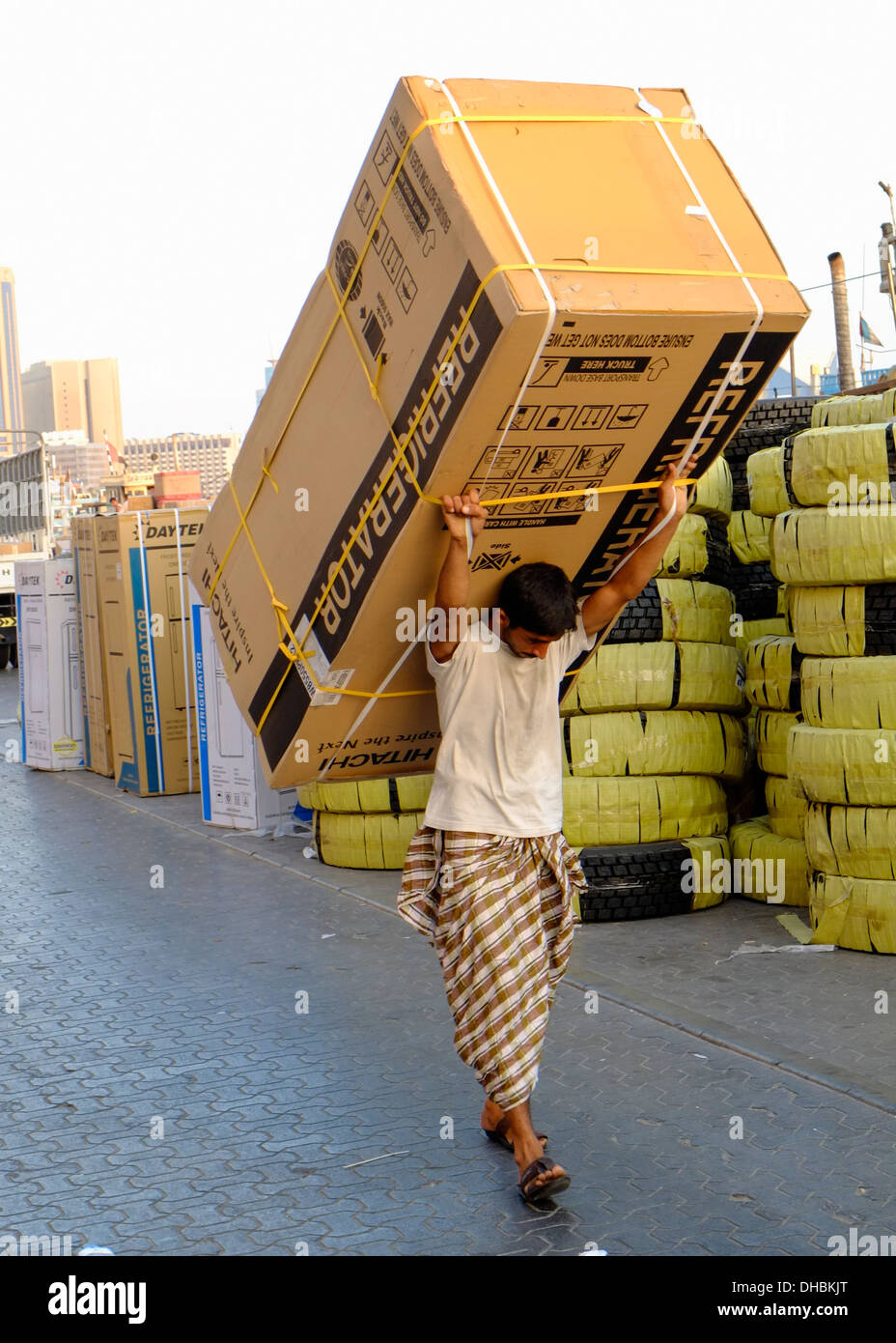 Man carrying cargo for loading onto a dhow at the Creek river in Dubai United Arab Emirates UAE - Stock Image