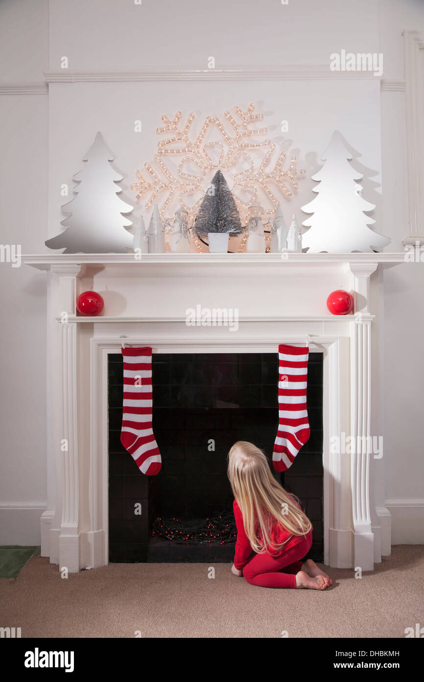 A young girl looking expectantly up the chimney awaiting the arrival of Father Christmas. - Stock Image