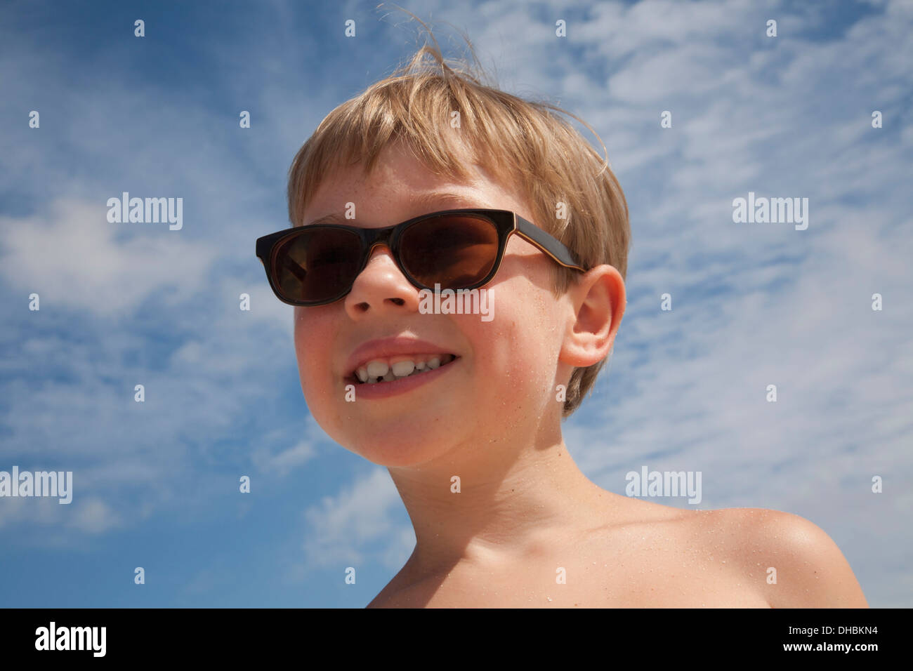 A young boy wearing sunglasses. Smiling, Blue sky. Blonde hair. - Stock Image