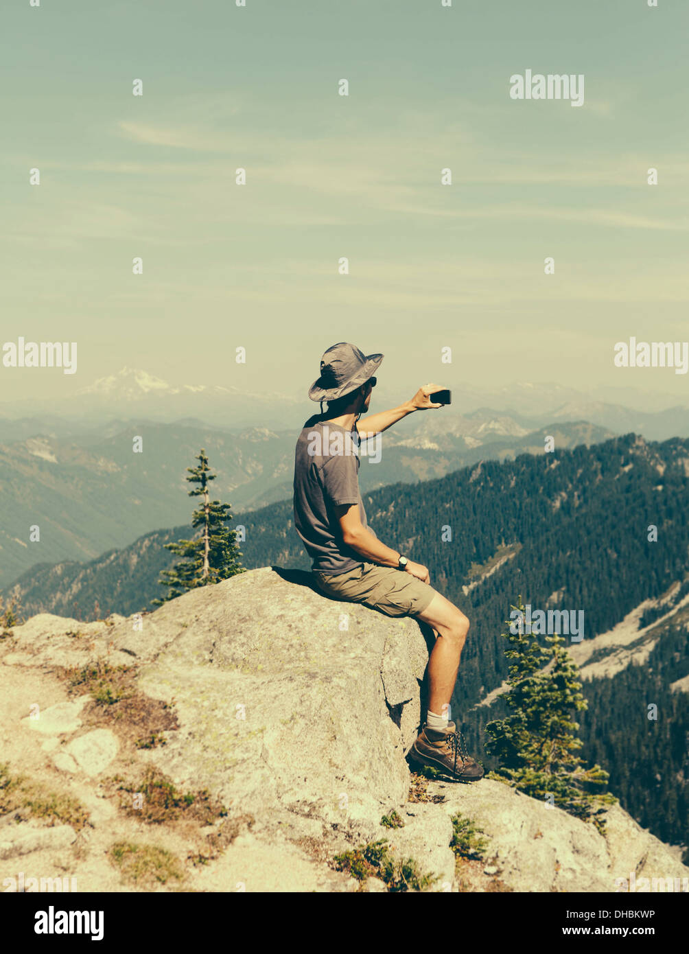 A hiker on mountain summit holding smart phone at top Surprise Mountain in Alpine Lakes Wilderness in Mount Baker-Snoqualmie - Stock Image