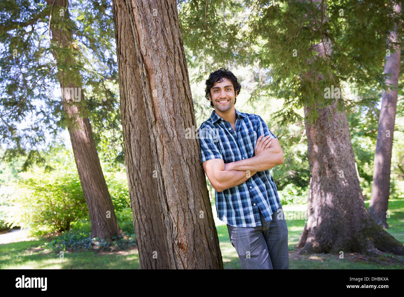 A farm growing and selling organic vegetables and fruit. A man leaning against a tree. - Stock Image