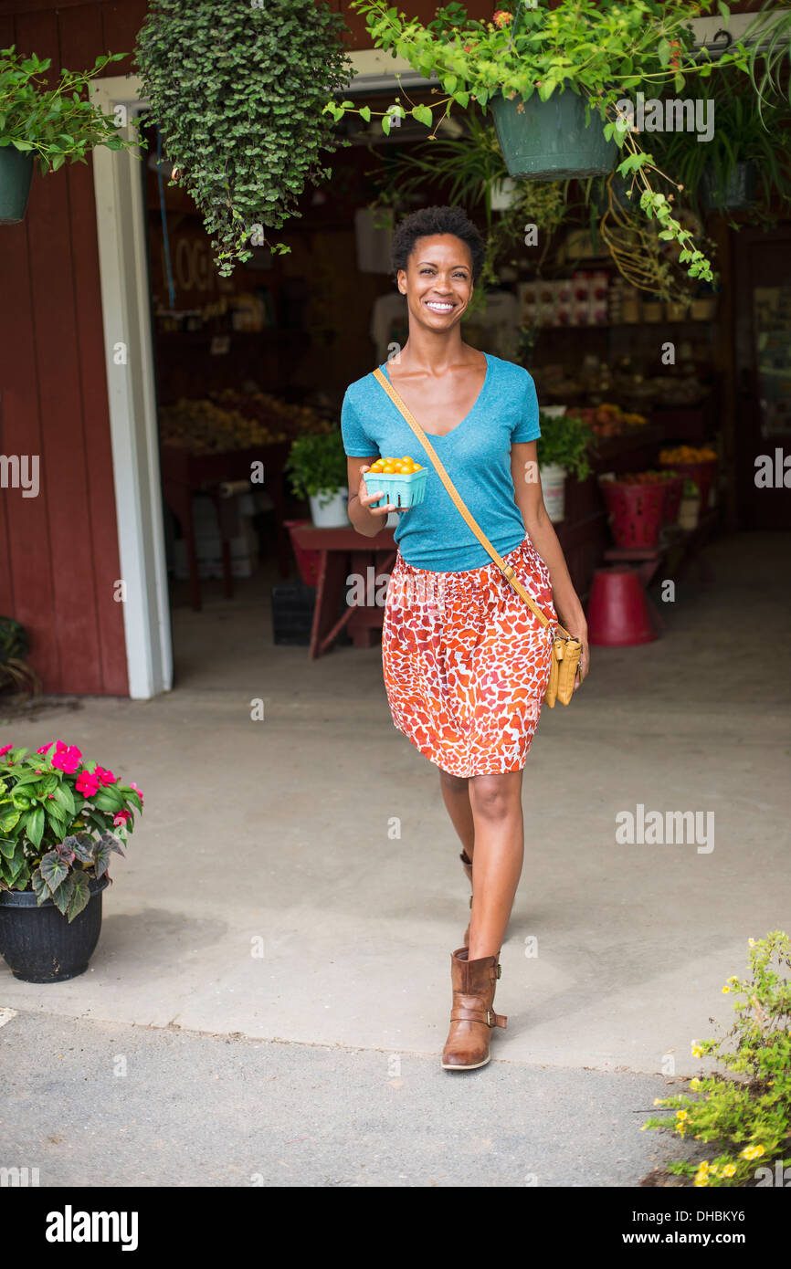 Working on an organic farm. A woman customer leaving the farm stand carrying fresh vegetables. Stock Photo