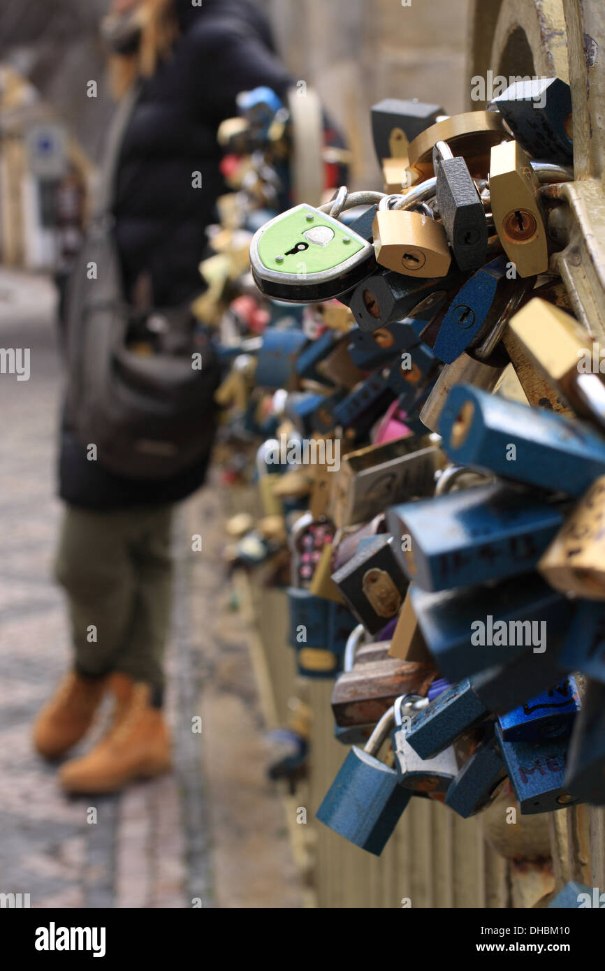 Love Locks at Charles Bridge, a woman standing in the distance, wearing beige boots and a black coat. - Stock Image