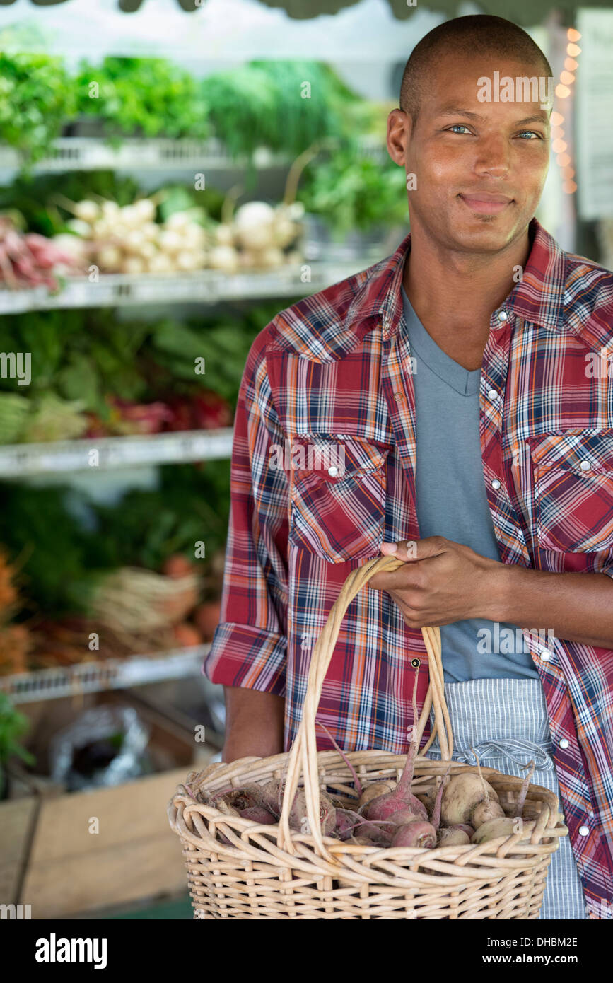 A farm stand with fresh organic vegetables and fruit.  A man holding bunches of carrots. Stock Photo
