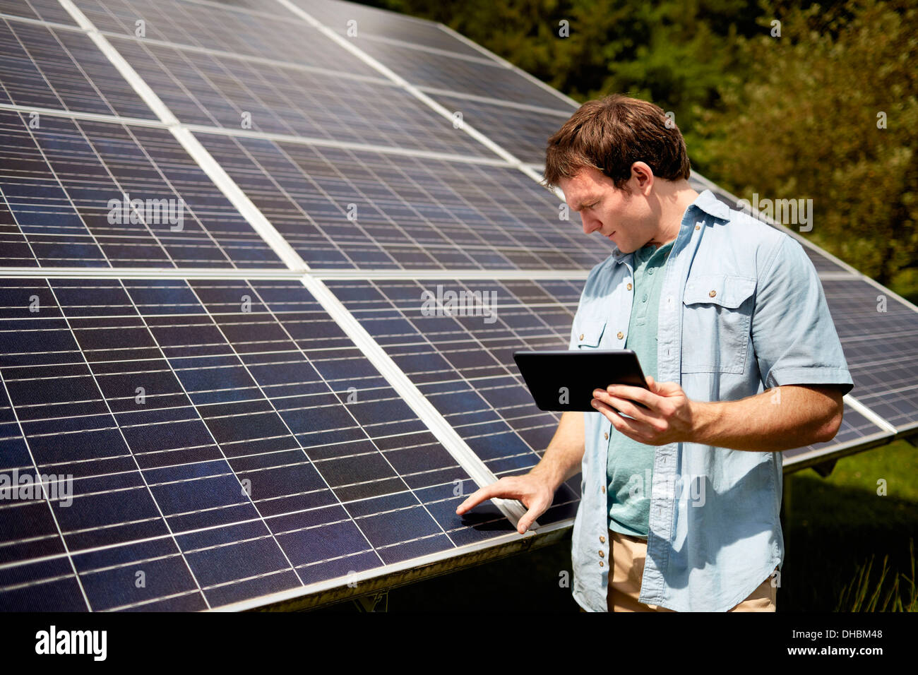 A farmer closely inspecting the surface of a solar panel on the farm. - Stock Image