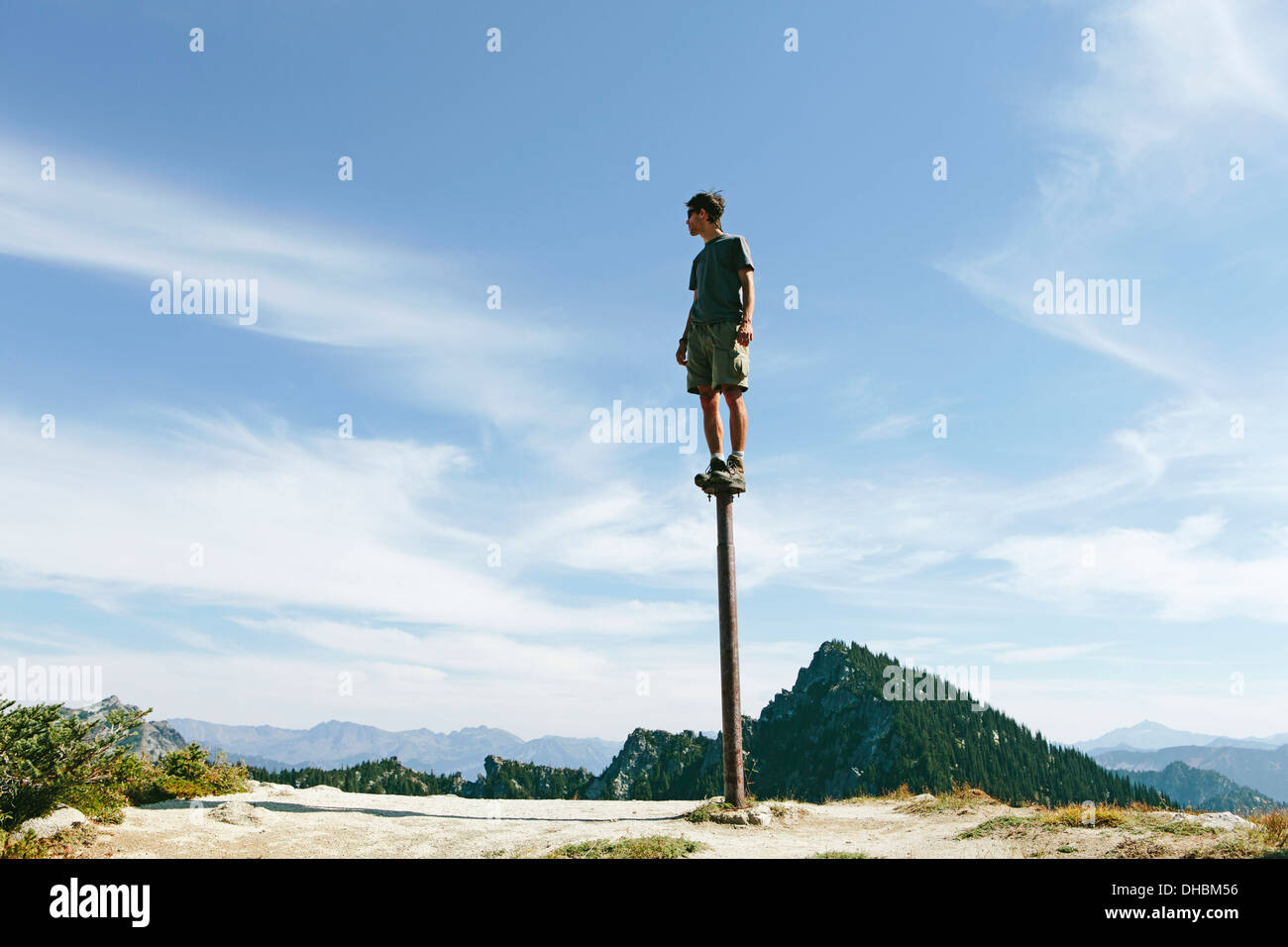 A man standing balancing on metal post looking towards expansive sky on Surprise Mountain Alpine Lakes Wilderness Mt - Stock Image