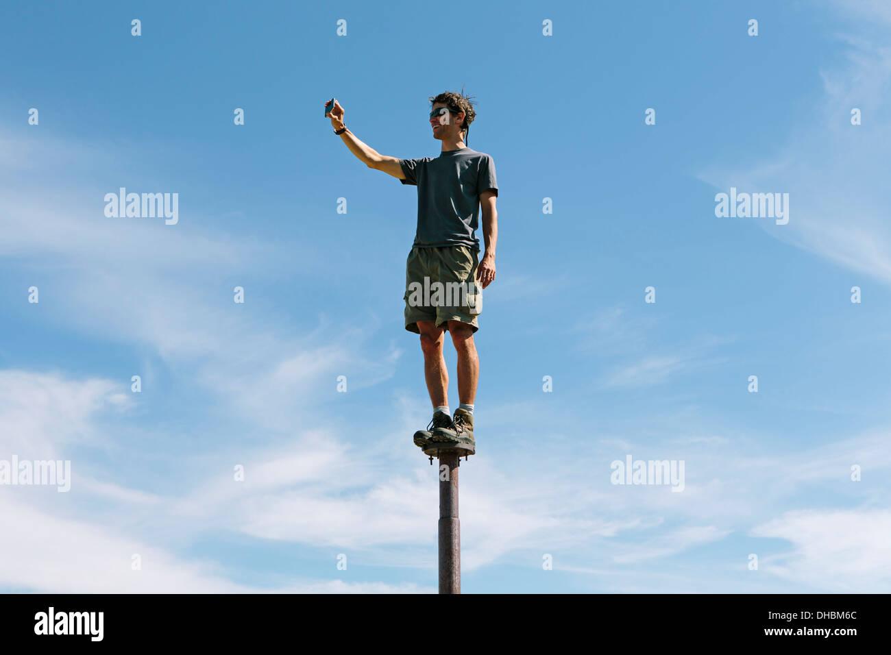 Man standing balancing on metal post looking towards expansive sky on Surprise Mountain Alpine Lakes Wilderness Mt - Stock Image