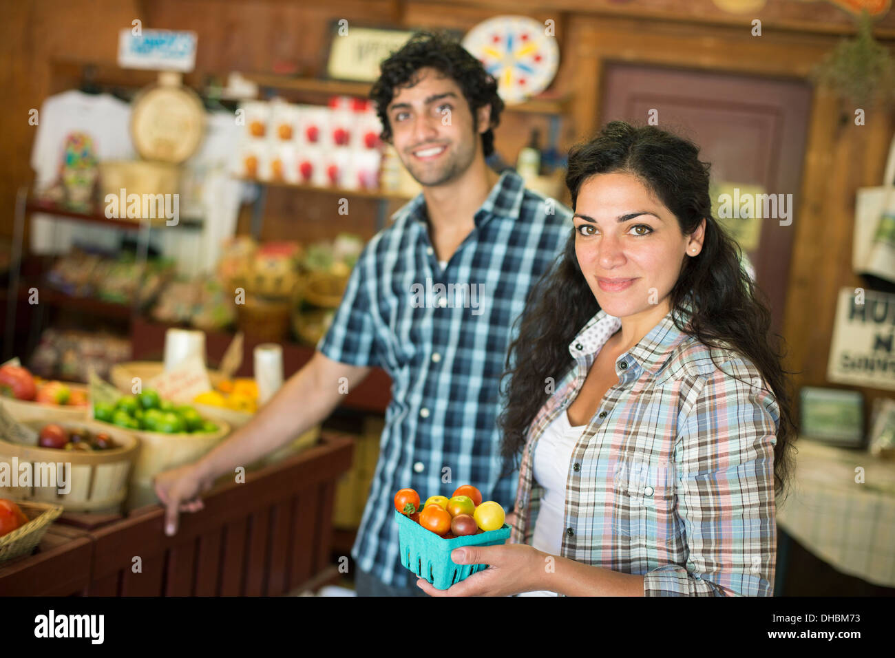 A farm growing and selling organic vegetables and fruit. A man and woman working together. - Stock Image