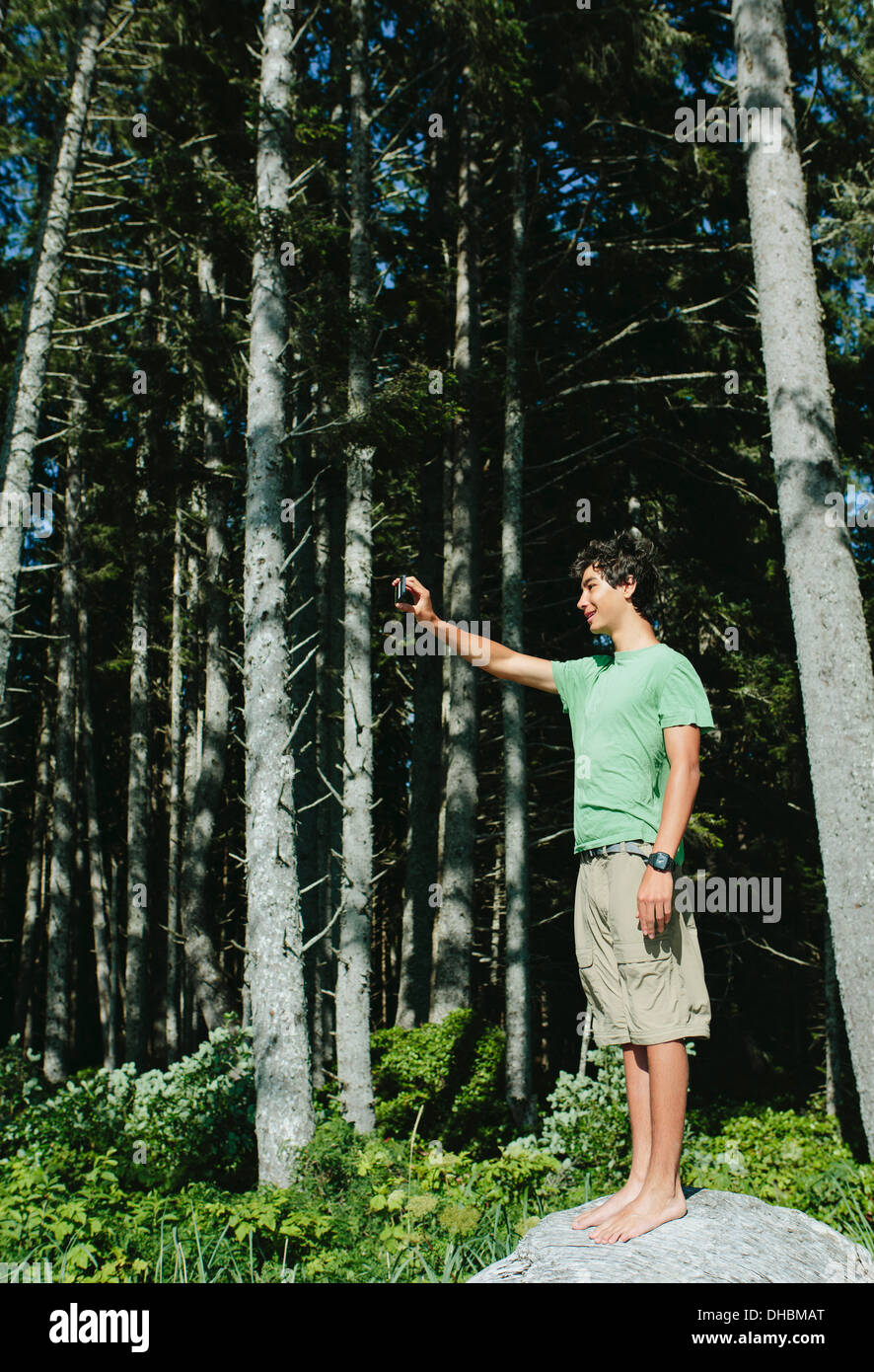A young boy standing in the forest holding a smart phone up to take a selfy or a photograph, in Olympic national park. - Stock Image