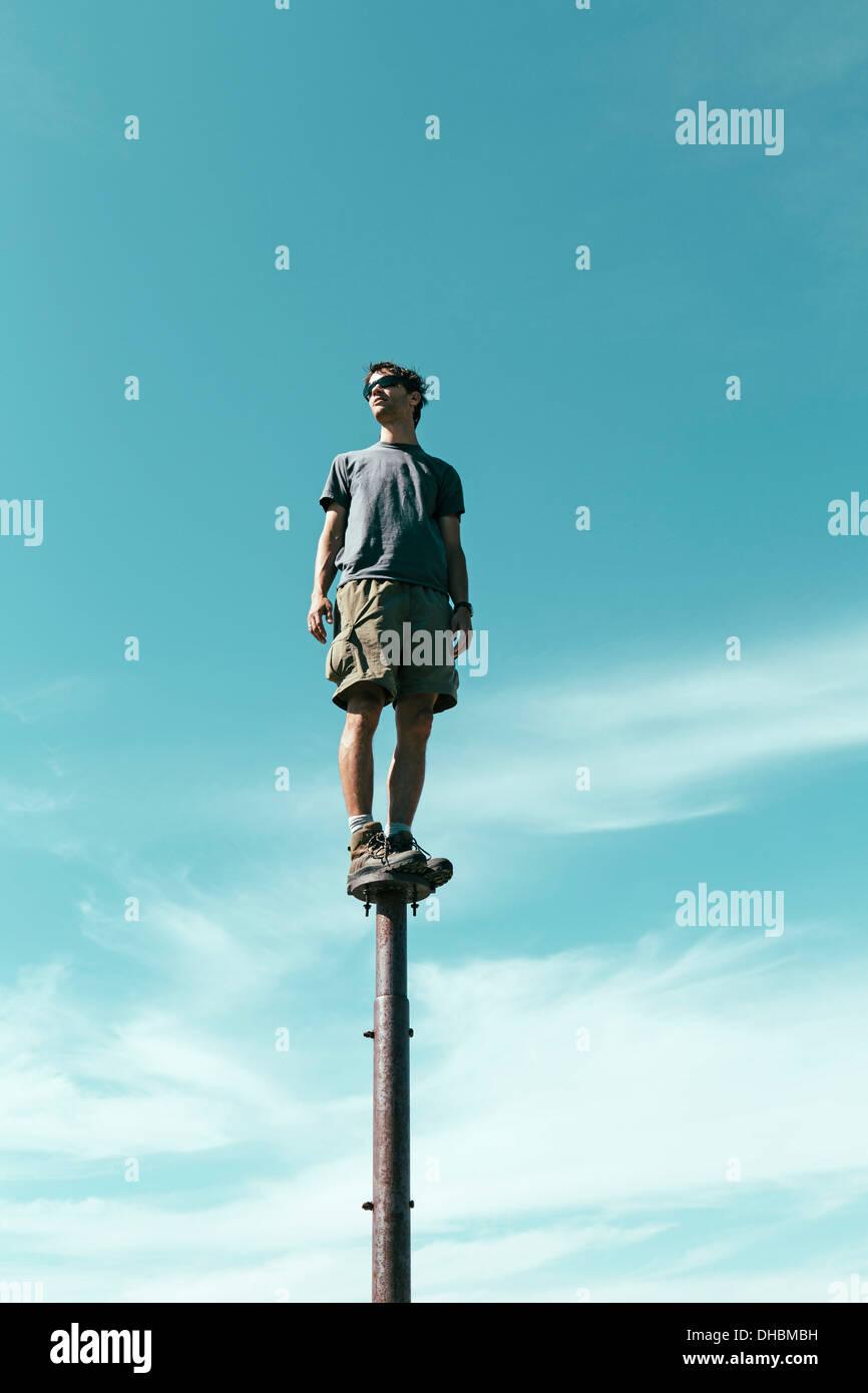 Man standing balancing on metal post looking towards expansive sky Surprise Mountain Alpine Lakes Wilderness Mt - Stock Image