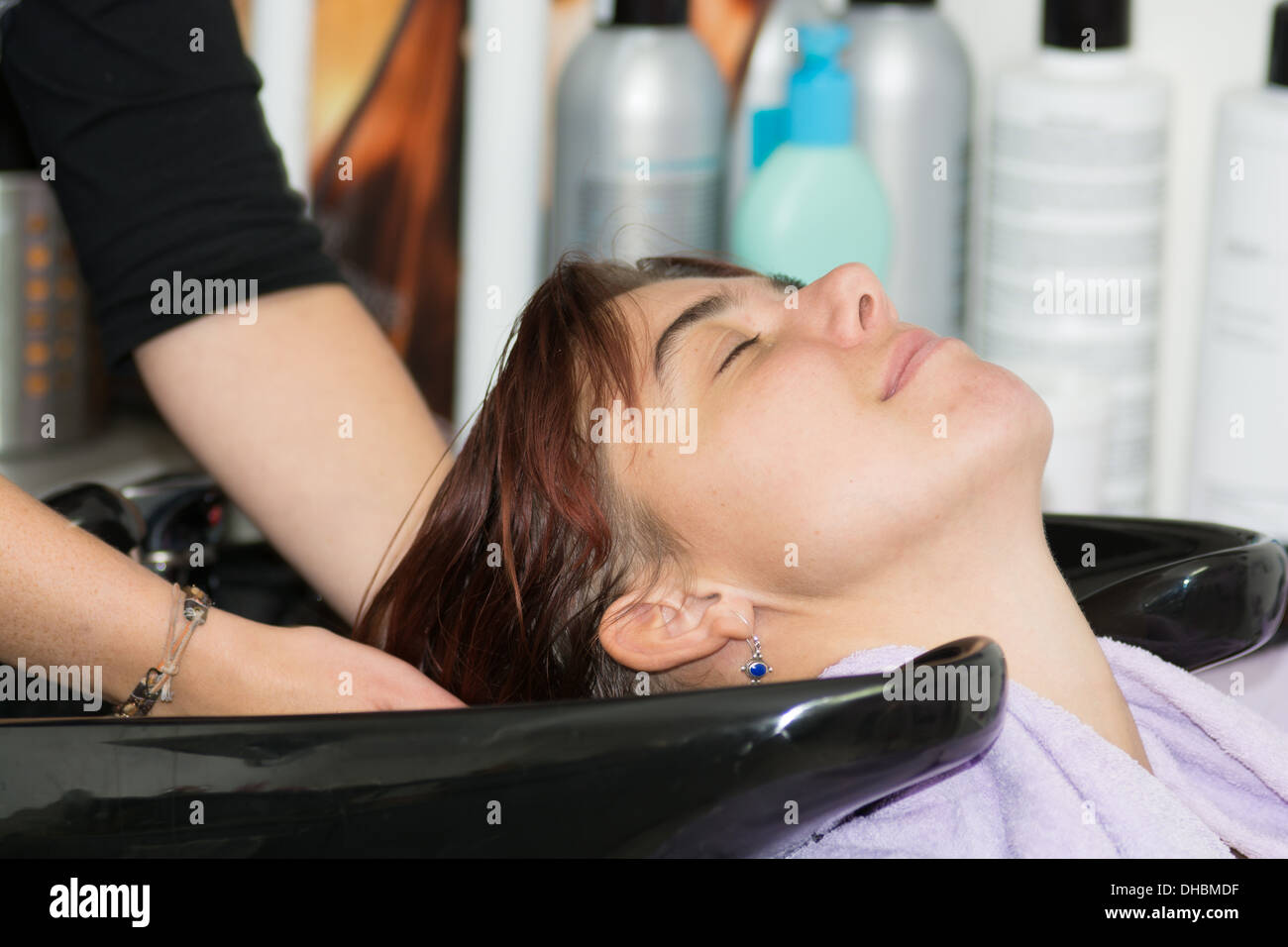 hair care - young woman enjoing hair washing at a hairdresser - Stock Image